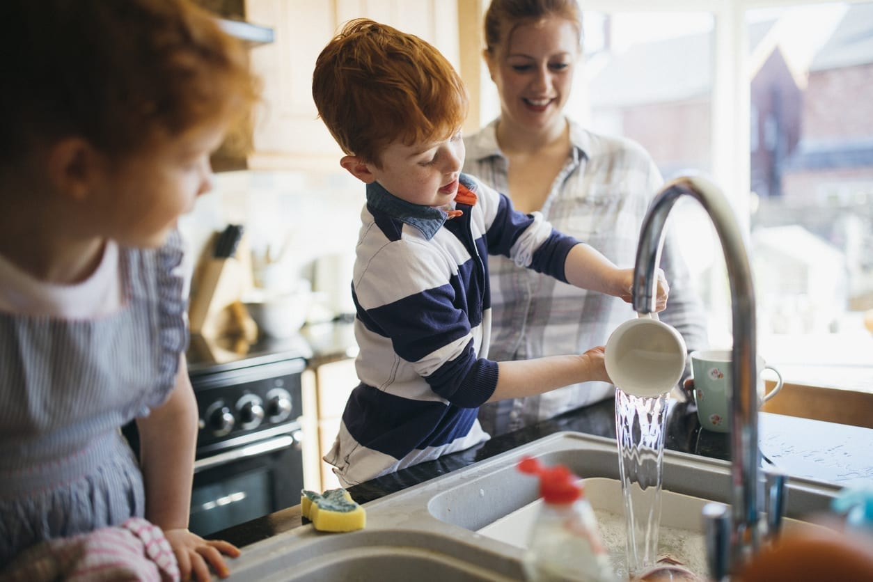Two children and their Mother washing the dishes in the kitchen sink.