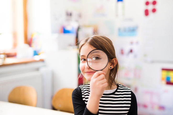 A small girl with a magnifying glass sitting at the desk at school.