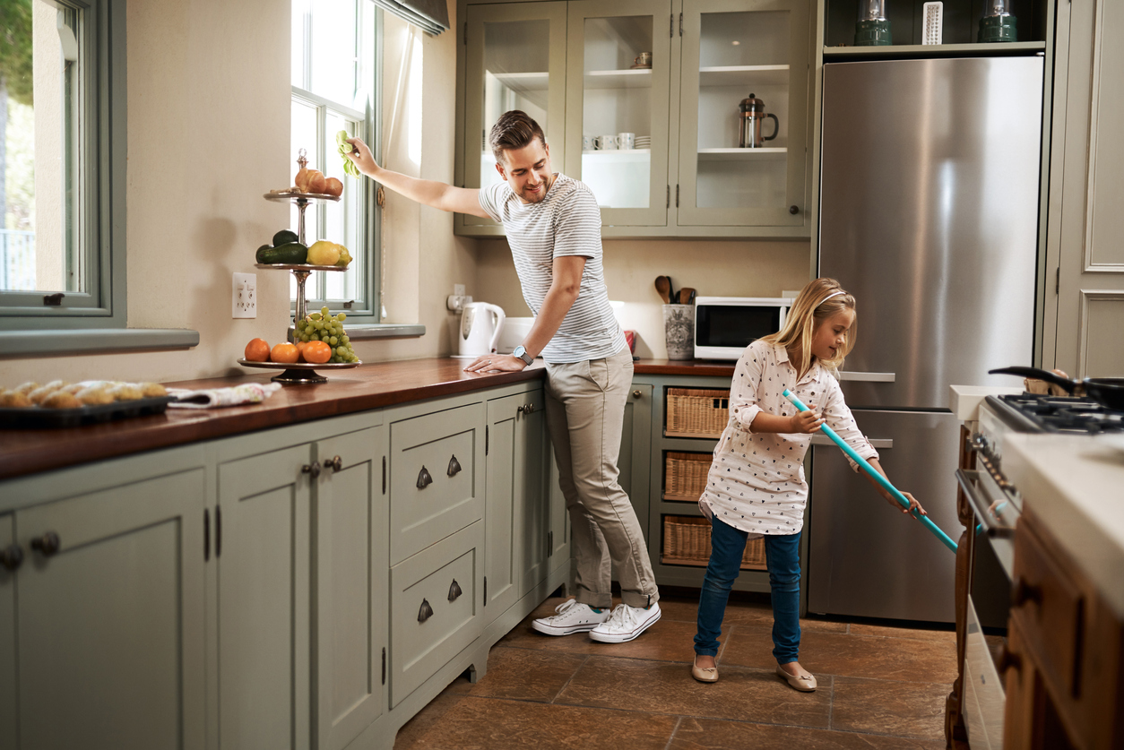 father and daughter cleaning the kitchen